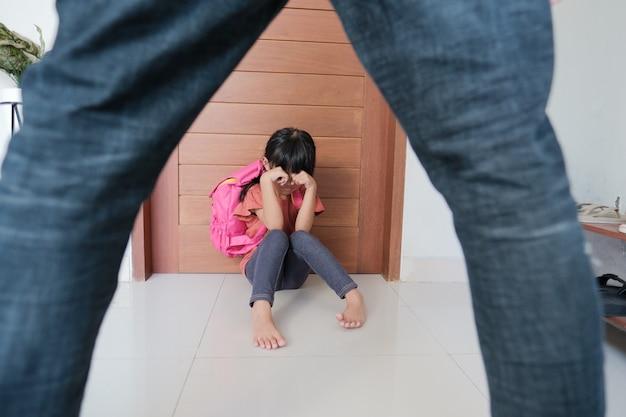 Жестокие родители пытаются ударить своего ребенка дома. отец и дочь домашнее насилие