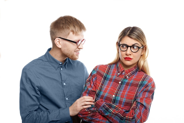 Abusive young man with stubble trying to intimidate blonde woman in checkered shirt, pulling her by sleeve. caucasian female being abused by bearded male, looking at him with eyes full of terror