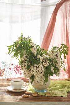 Цветы акации в белой вазе