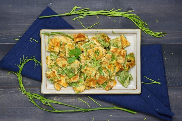 나무 테이블에 식탁보가 있는 접시에 아카시아 펜나타 오믈렛, 태국 현지 음식
