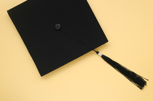 Academic cap on yellow background