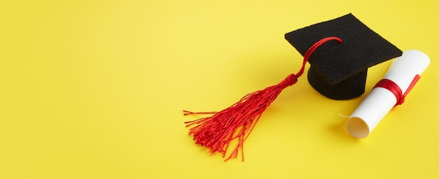 Academic hat with diploma on yellow background graduation theme