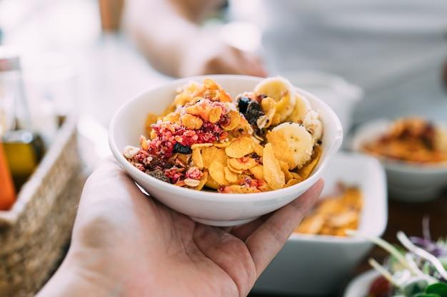 アサイーボウルに新鮮なマンゴー、アボカド、バナナ、ベリー、ヒマワリの種、チアシード、シリアルを混ぜます。