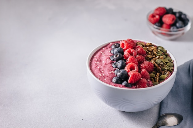 Acai bowl of smoothies with berries, walnuts, pumpkin seeds and sesame