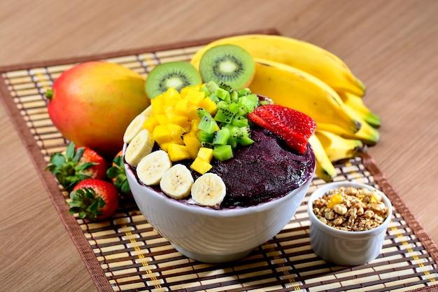 Acai bowl with fruits salad banana mango kiwi and strawberry