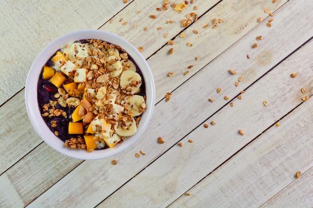 Чаша асаи с манго, бананом, семенами льна мюсли и сгущенным молоком на белом деревянном столе
