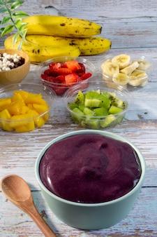 Чаша асаи на деревянном столе свежие фрукты на заднем плане