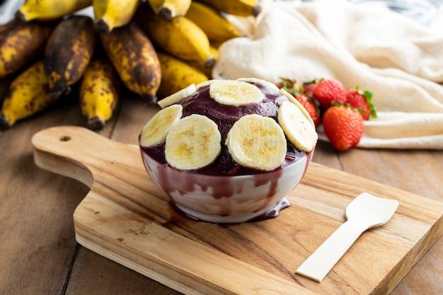 Асаи, бразильское мороженое из замороженных ягод асаи с бананами. с фруктами на деревянном столе. вид спереди летнее меню