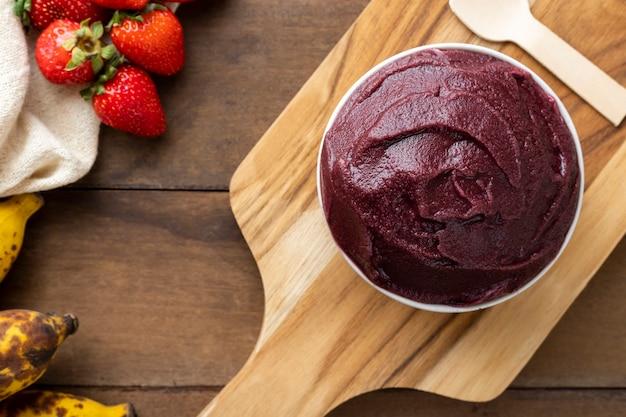 アサイ、ブラジルの冷凍アサイベリーアイスクリームボウル。木製のテーブルに果物と。夏のメニュー上面図