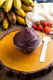 Асаи, бразильское мороженое из замороженных ягод асаи с клубникой и бананами. с фруктами на деревянном столе. вид спереди летнее меню