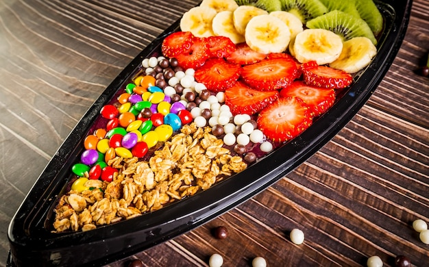 Acai frozen with banana, kiwi fruit, granola and candies for share.