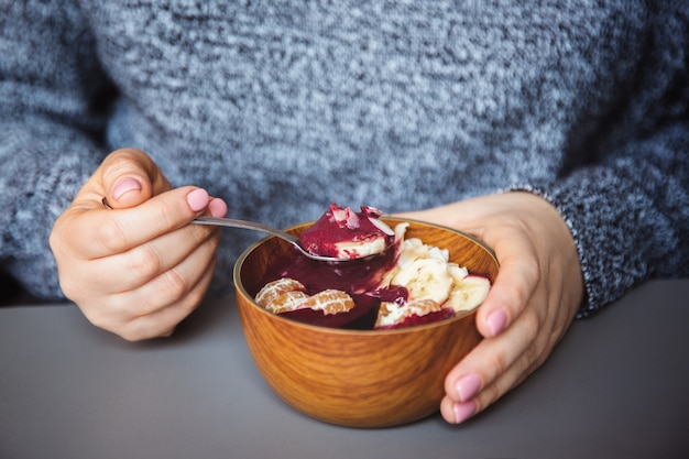 Acai smoothie, granola, seeds, fresh fruits in a wooden bowl in female hands on grey table
