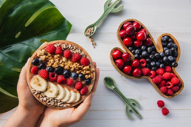 Acai smoothie, granola, seeds, fresh fruits in a wooden bowl in female hands with cactus spoon. plate filled with berries
