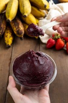 アサイ、ブラジルの冷凍アサイベリーアイスクリームボウルを持っている女性。木製のテーブルに果物と。夏のメニュー正面図