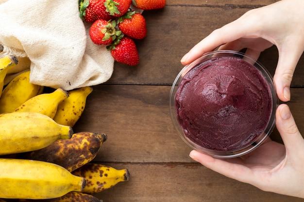 アサイ、ブラジルの冷凍アサイベリーアイスクリームボウルを持っている女性。木製のテーブルに果物と。夏のメニュー上面図