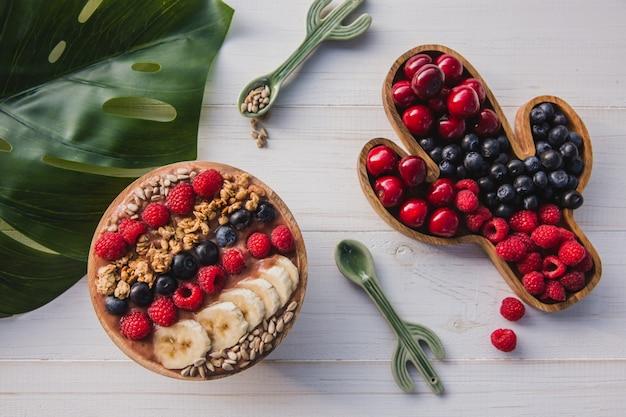 Acai пюре, мюсли, семена, свежие фрукты в деревянной миске с ложкой кактуса. тарелка с ягодами