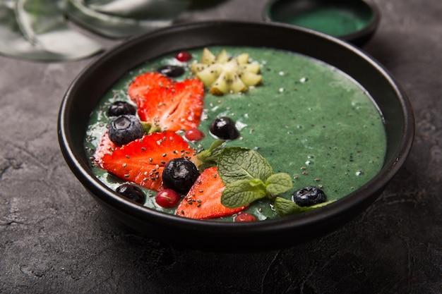Красочная, здоровая еда. acai чаша смузи. кето идея для завтрака. фруктовый творожный смузи, асаи. завтрак с зеленой спирулиной, клубникой, чиа, киви в черной тарелке