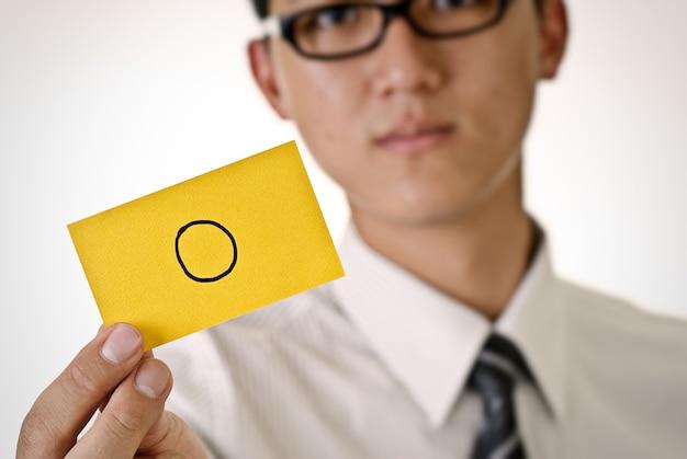 ビジネスマンが保持しているイエローカードのパターンを受け入れる