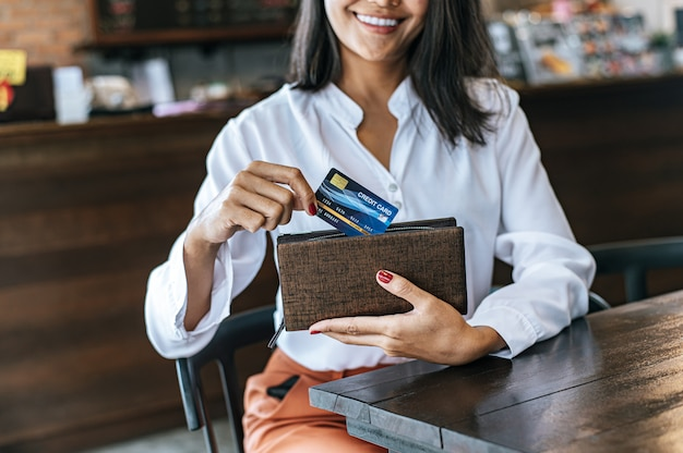 Accepting credit cards from a brown purse to pay for goods