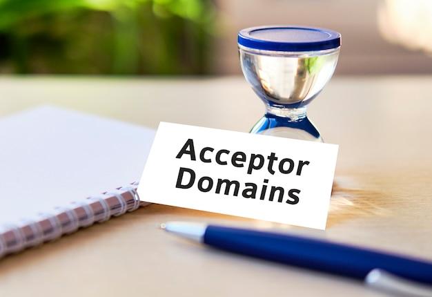 Акцепторные домены - бизнес-концепция seo текст на белом блокноте и песочные часы, синяя ручка, зеленые листья цветов