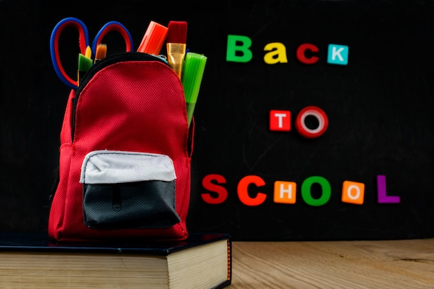 Accesories in student bag  with black chalk board. back to school text.