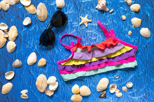 Accesories for summer sea beach on blue wawes background. beach things sunglasses and swim suit