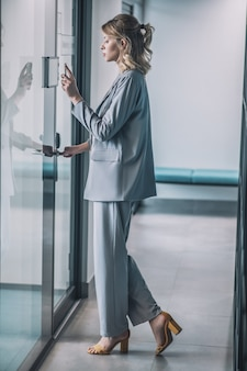 Access control system. young slender woman in business suit with high heels standing in corridor in front of her office door