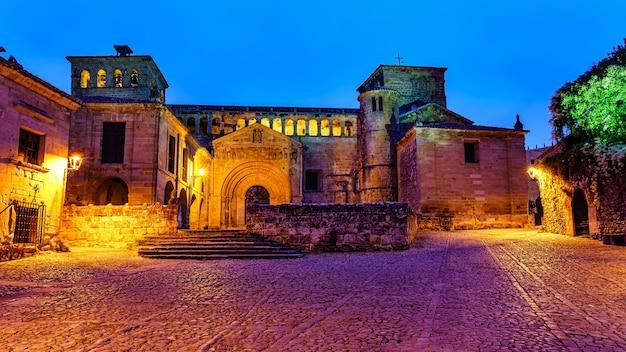 夜に街灯に照らされた中世の教会へのエスプラネードにアクセスします。サンティリャーナデルマール。