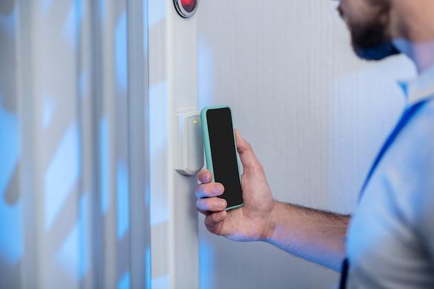 アクセス許可。チェックポイントでアクセス許可を待っているスキャンデバイスにスマートフォンを適用する男性の手