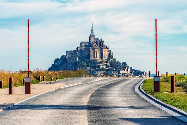 Access road to mont saint michel with a raised barrier. access is restricted, only authorized vehicles have access.