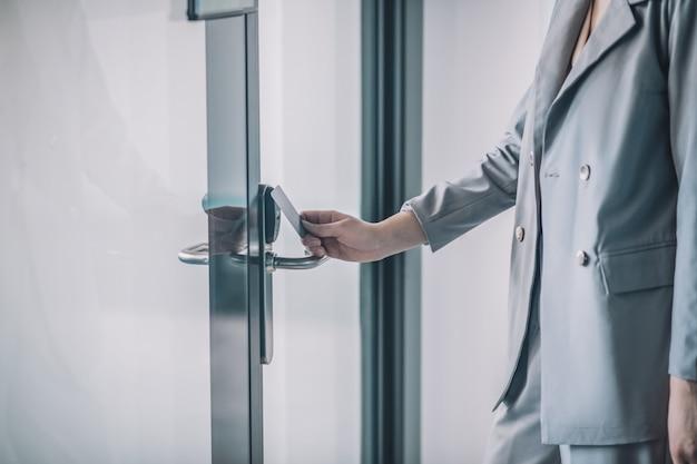 アクセスシステム。パスカードでオフィスのドアを開く灰色のビジネススーツの女性の手