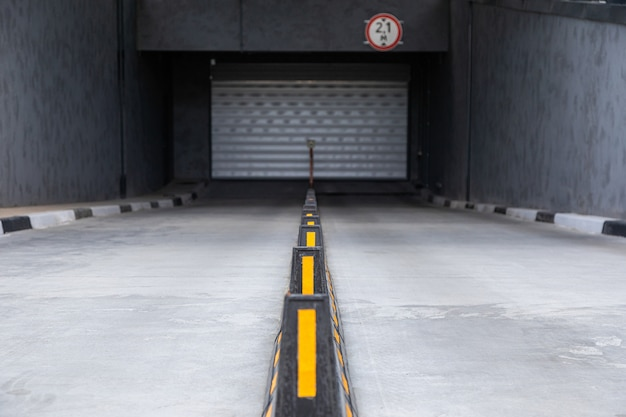 Access to underground car park with roller-shutter door and road dividers with yellow sticks