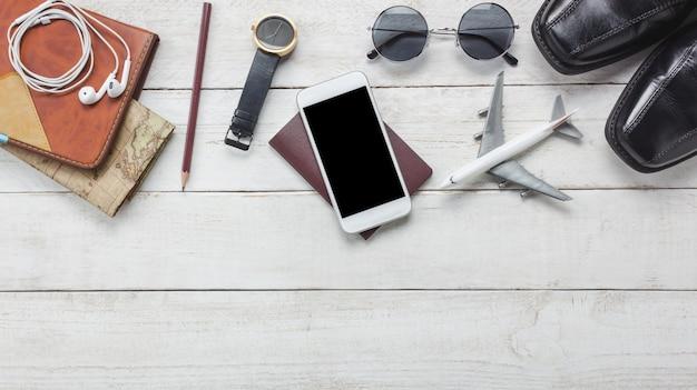 トップビューのaccessoires旅行concept.white携帯電話と木製の背景にヘッドホン。航空機、マップ、パスポート、木製のテーブルで腕時計。
