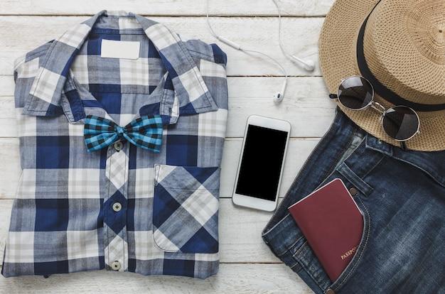 トップビューaccessoires男性服のコンセプトで旅行する。シャツ、ジーンズ、木製の背景上のヘッドフォンで音楽を聞く携帯電話。パスポート、キー、サングラス、木製テーブル上の帽子。