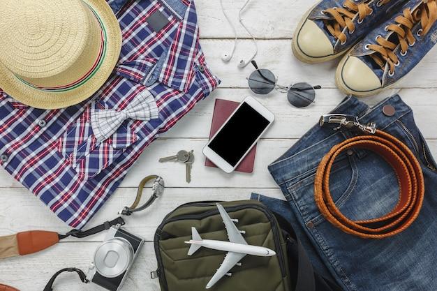 トップビューaccessoires男性服のコンセプトで旅行する。シャツ、ジーンズ、携帯電話、木製の背景上のヘッドホン。パスポート、キー、サングラス、帽子、木製テーブル。