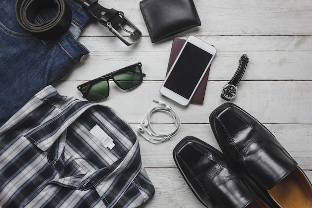 トップビューaccessoires男性服のコンセプトで旅行する。シャツ、ジーンズ、木製の背景上の携帯電話。ウォッチ、サングラス、木製テーブル上の靴。