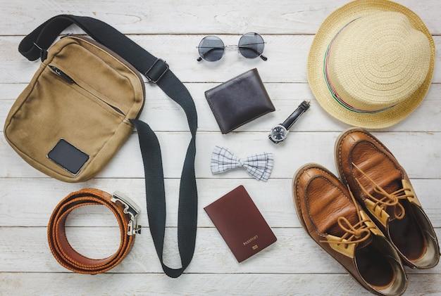 トップビューaccessoires男性服のコンセプトで旅行する。蝶ネクタイ、木製の背景にウォレット。ウォッチ、サングラス、バッグ、帽子、ベルト、木製テーブル上の靴。