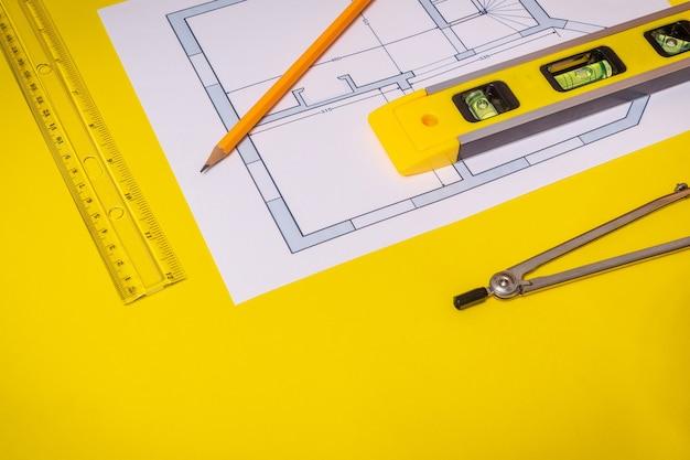 Аксессуары и инструмент для рисования лежат на строительном проекте на желтом рабочем столе Premium Фотографии