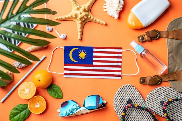 Accessories for beach holidays around a protective mask with the flag of malaysia