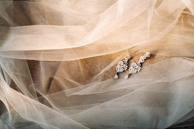 Accessories for the bride. earrings on the veil. white wedding earrings. space for text and ads.