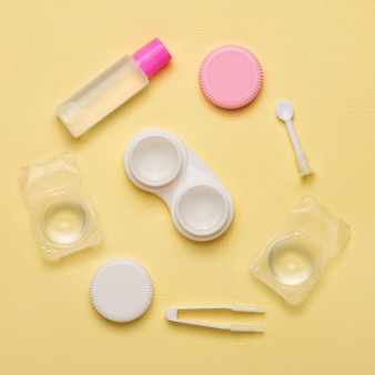 Accessories for contact lenses on a yellow background