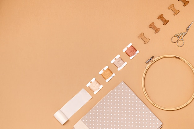 Accessories for cross stitch on a beige background, flat lay, copy space.