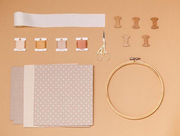 Accessories for cross stitch on a beige surface, flat lay, copy space