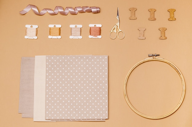 Accessories for cross stitch on a beige surface
