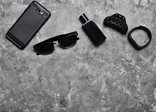 Аксессуары для деловой женщины на бетонном столе. кошелек, парфюм, солнцезащитные очки, умные часы, смартфон, ручка. рабочее пространство. монохромная фотография. тенденция минимализма. вид сверху.