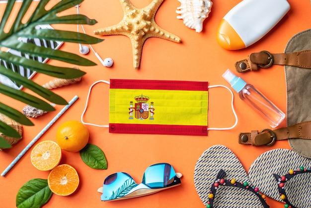 スペインの旗が付いている防護マスクの周りのビーチでの休暇のためのアクセサリー