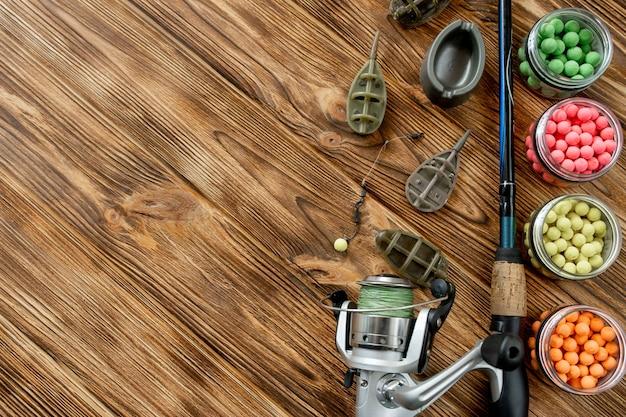 コピー スペース付きの木製の板に鯉釣りや釣り餌のアクセサリー。