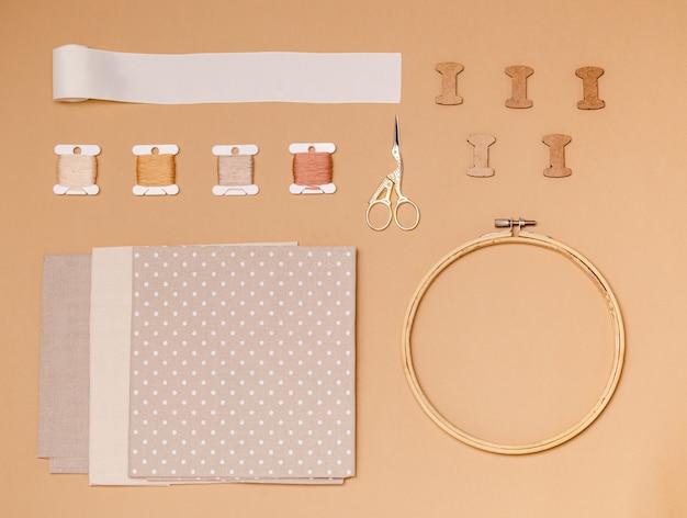 Аксессуары для вышивки крестом на бежевой поверхности, плоская планировка, копировальное пространство