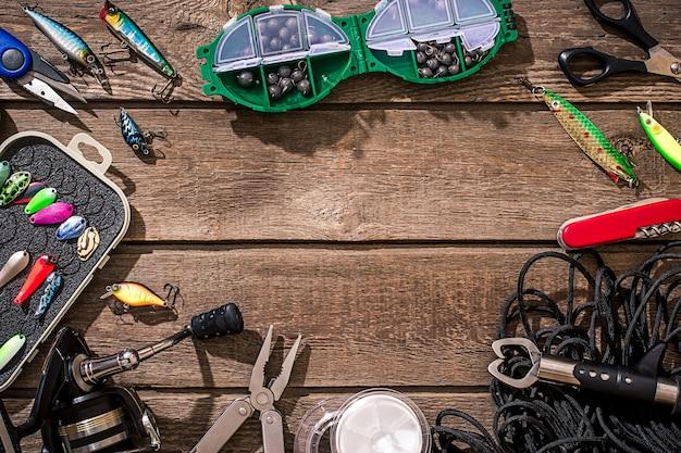 木の背景に釣り用アクセサリー。リール、釣り糸、フロート、ネットフック、釣り用ルアー。上面図。静物。コピースペース