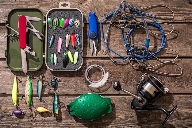 Аксессуары для рыбалки на фоне дерева. катушка, леска, поплавок, сетевые крючки, приманки для рыбалки. вид сверху. натюрморт. копировать пространство
